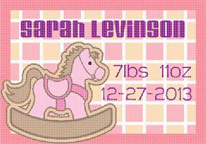 Birth announcement for a baby girl, featuring a pink wooden toy horsie against a boxy background.