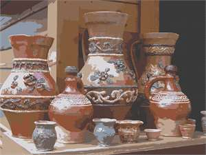 A collection of ceramic vases, pitchers, and cups on display.
