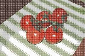 Some vine tomatoes on a pretty tablecloth.