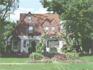 A picturesque scene of a cottage surrounded by foliage and blossoms.  A beautiful landscape needlepoint.