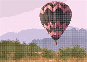 The pink-and-chocolate chevron hot air balloon hovers over the desert landscape.