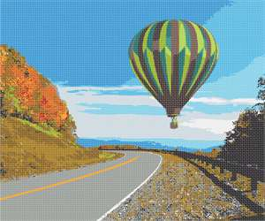 The bright green hot air balloon hovers silently over the cross-mountain highway.