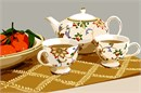 Teapot, teacups and a bowl of oranges on a gold trellis vine table runner