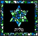 Stained glass design in shades of blue and green. Star of David with frame and space below for Hebrew text.  Stained glass design is very popular on many Judaica items. You stitch the front. After it is completely stitched, it is sent to a professional finisher who adds a lining, back, and matching zipper.