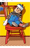 The well-known rag doll, sitting handsomely in a wicker chair.
